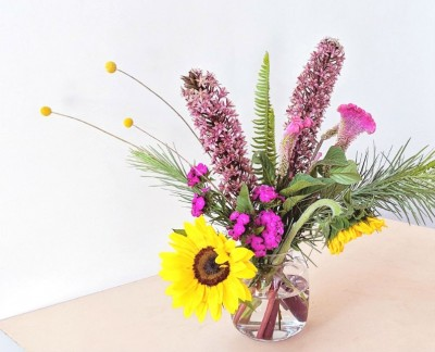 Mardi Gras Inspired colourful flower arrangement with sunflowers and pineapple lilies
