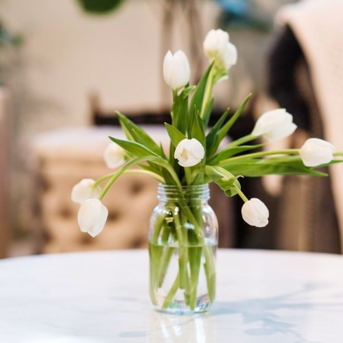 10 stems of white tulips in glass jar